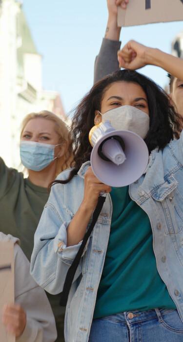 Eine Gruppe von jungen Menschen protestiert mit Schildern und einem Megafon