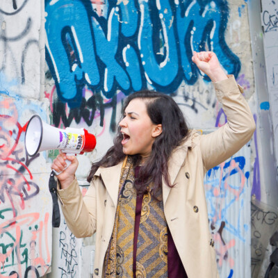 Frau mit erhobener Faust und Megafon in der Hand vor einer Graffti-Wand