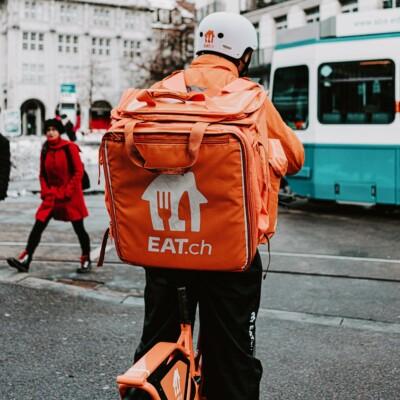 Lieferperson mit einem orangenen Rucksack auf einem Fahrer auf der Straße